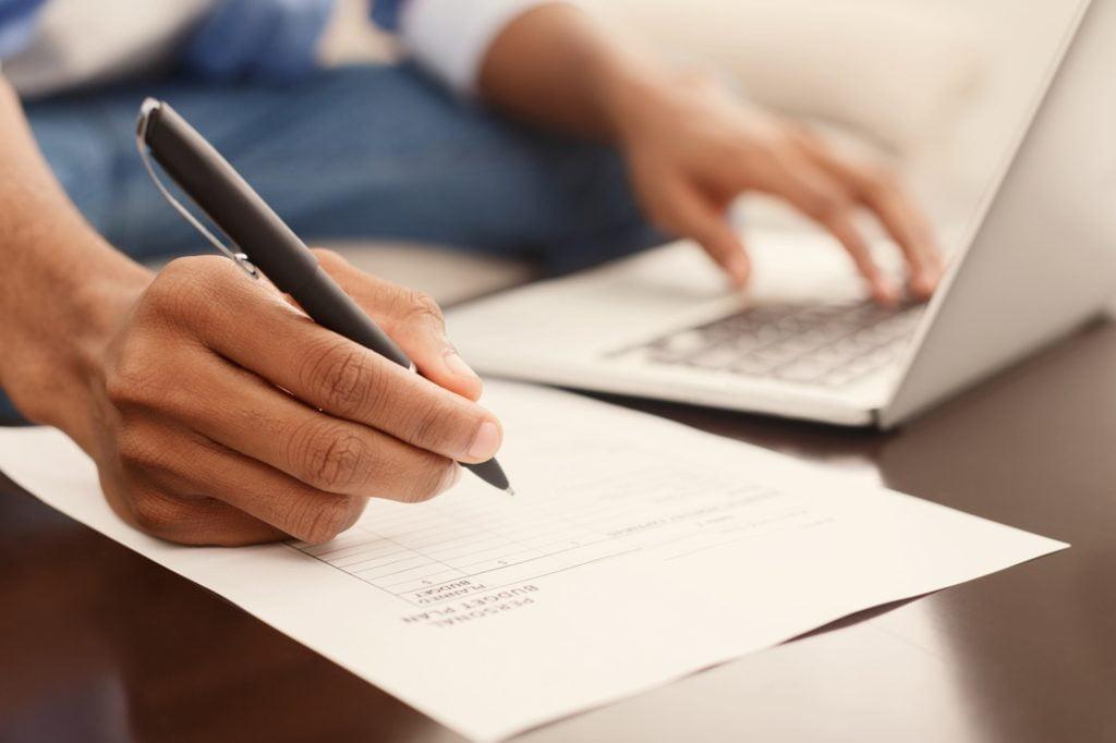 Financier making annual financial report using laptop